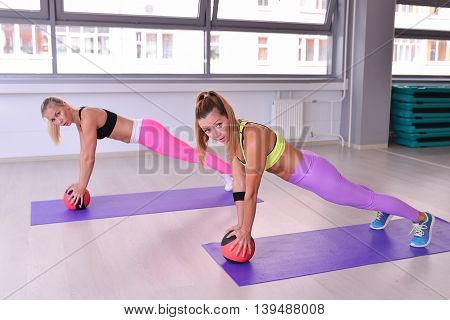 Muscular women doing plank exercise with a ball in fitness club.