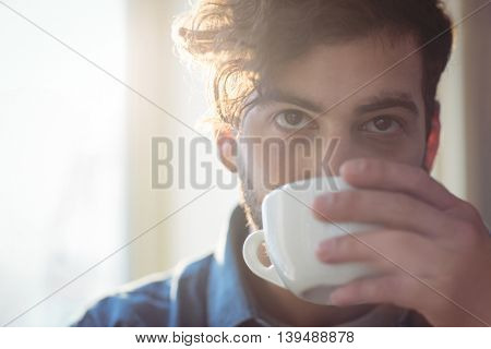 Close-up of young male customer drinking coffee at cafe