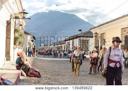 Antigua Guatemala - February 15 2015: Tourists and locals stroll the streets of the beautiful colonial city of Antigua on a sunny day. Maya woman is seen on the left selling traditional woven crafts. Agua volcano far on the background