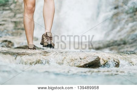 Unrecognizable hiker young woman walking along mountain river in summer outdoor view of legs close-up