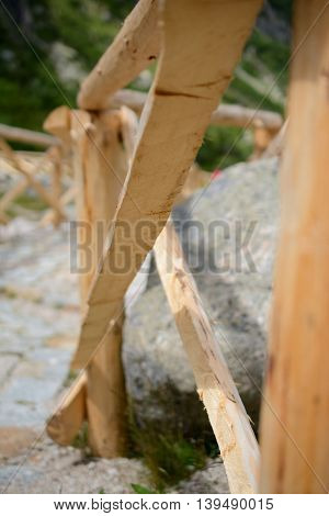 Part of new wooden barrier made of fresh raw wood at trail. Shallow depth of field.