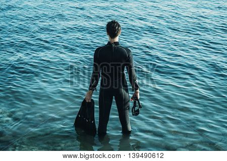 Young man wearing in a diving suit with flippers standing in the sea in summer rear view