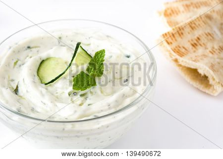 Tzatziki sauce with cucumber in bowl and pita bread isolated on white background