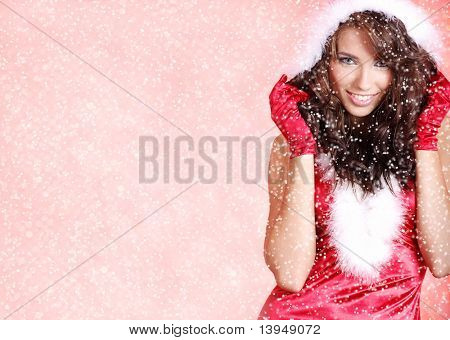 Portrait of beautiful woman wearing sexy santa claus clothes on snow flakes red background