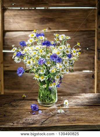 Bouquet of chamomiles and cornflowers in the vase on the wooden table.