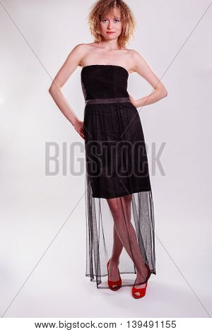 A beautiful young woman posing in a chic black dress in an urban setting