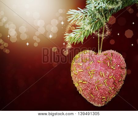 Christmas decorations in the form of heart on fir branch with bokeh