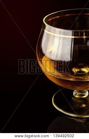 Shot glass with alcohol against a dark background. Part of a shot glass against a dark background with reflection. Vertical format. Indoors. Color. Photo.