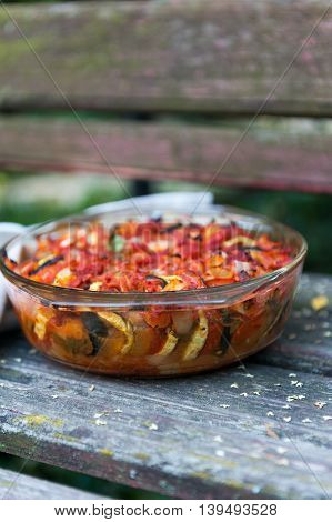 Close up of a wooden table with a casserole with ratatouille