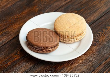 Two Traditional French Chocolate Macarons On Plate, Wooden Background