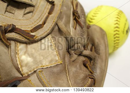 Softball glove in focus with blank tag and yellow softball in background