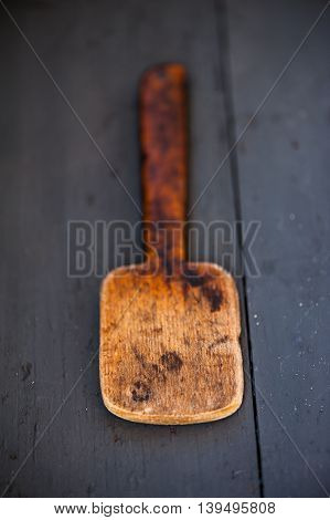 Close up of an old wooden spatula on a wooden table