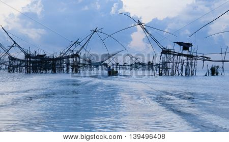 Fisherman with sunrise at Pakpra, Phatthalung Province,Thailand.