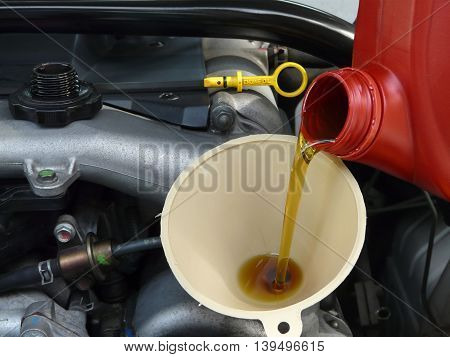 Motor oil from a red jug is being added with a funnel from the right side of a car. Yellow dipstick and cap are nearby.