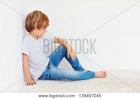 Cute Boy, Kid Sitting Near The Wall