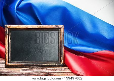 Russian flag on a wooden table and a black board for your text. vignetting for artistic effect