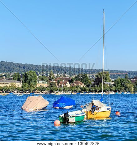 Boats on Lake Zurich in summertime, city of Zurich in the background.