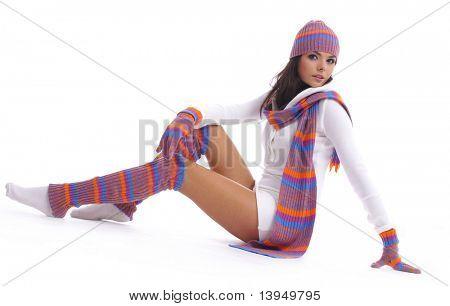 sexuelle Mädchen in ein multicolor Mütze und Handschuhe legt auf White FuГџboden. Wintermode.