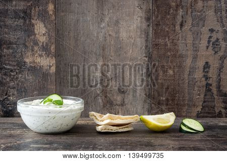 Tzatziki sauce and pita bread on rustic wooden background