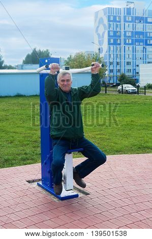 An elderly man is at the gym on the street in Niznnekamsk town (Tatarstan Russia)