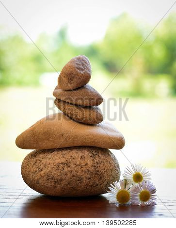 stone zen spa on wood with garden blurred