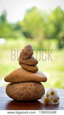 stone zen spa on wood with garden blurred