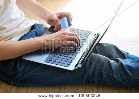 Man sitting shopping online using laptop at home