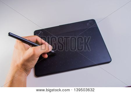 Graphic Tablet with men's hands. Man working on professional graphic tablet with pen