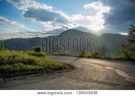 Sun shining on asphalt in the middle of hairpin curve