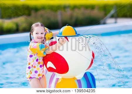 Happy laughing little girl playing in outdoor swimming pool on a hot summer day. Kids learn to swim with colorful floaties.