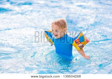 Happy laughing little boy playing in outdoor swimming pool on a hot summer day. Kids learn to swim with colorful floaties.
