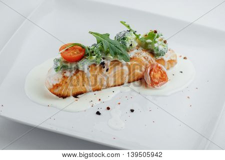 Red Fish On A White Plate With Tomato Sauce And Broccoli
