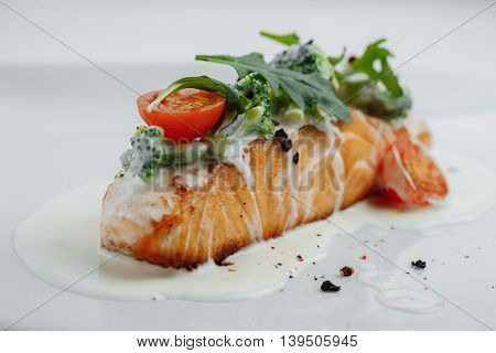 Red Fish In White Sauce With Tomatoes, Broccoli And Greens On White Background
