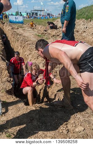 Tyumen, Russia - July 9, 2016: Steel Character extrim race on Voronino Hill. Running on a deep trench. The man helps the girl to get out to a surface