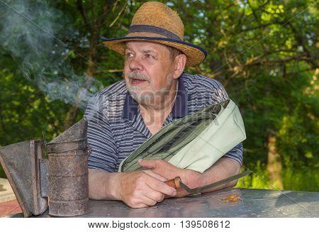 Outdoor portrait of positive bearded elderly man bee-keeper