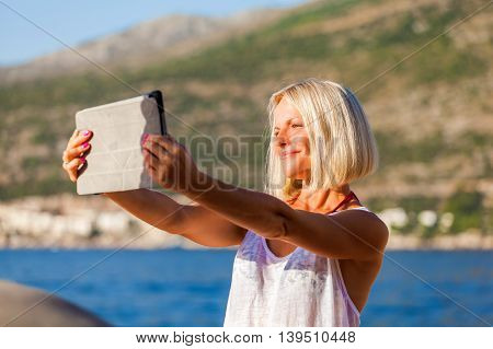 Young girl makes selfie photos with a tablet in the sea in summer. Summer vacation at sea. Dubrovnik. Croatia