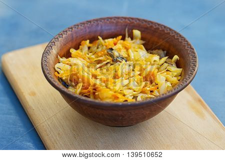 braised cabbage in a wooden bowl on the blue backgraund
