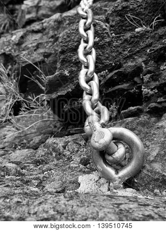 Steel Bolt Anchor Eye In Hard Basalt Rock. End Of Steel Chain