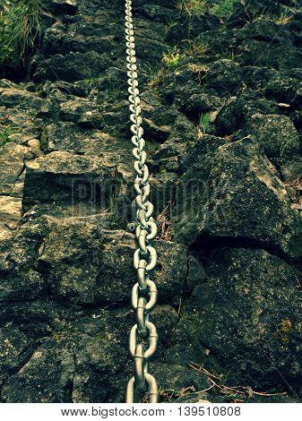 Detail Of Chain Anchored In Hard Whinstone Rock. Climbers Path