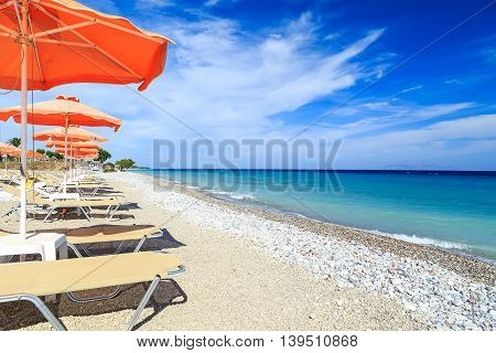 Orange beachchairs on a beach together with umbrellas