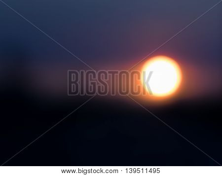 Abstract Sunrise or Sunset: bright, haloed sun setting in dark blue sky