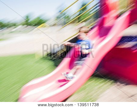Motion blue of young child sliding down playground slide