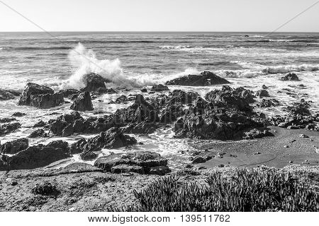 Black-and-White image of ocean waves rashing on rocky beach in California