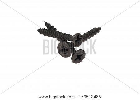 Three black metal screw lying on a white background