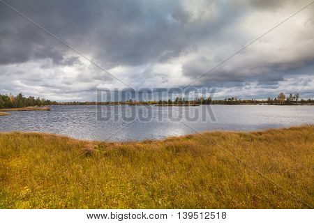 Autumn landscape on the lake and overcast sky