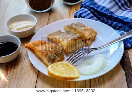 Fish fried pike in batter on a white plate wood table