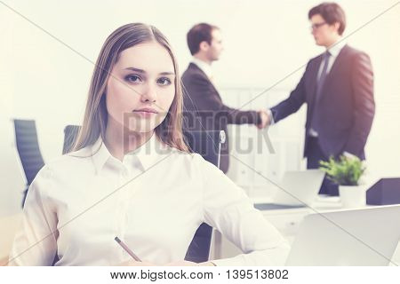 Businesswoman at laptop two businessmen shaking hands at background. Concept of work. Film effect