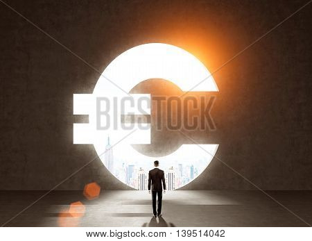 Businessman in dark suit standing in front of big Euro sign looking at New York ctiy at background. Concept of strategy for business development. Toned image