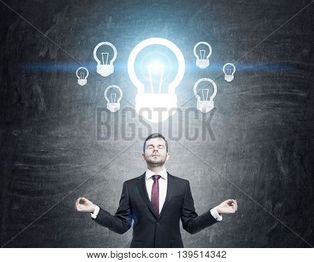 Businessman in suit with red tie meditating in front of chalkboard with light bulbs drawn on it. Blue light. Toned image