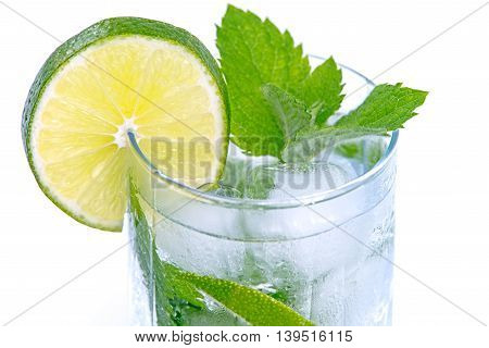 Mineral water with lime and ice cubes in wet and frosted glass on a white background.